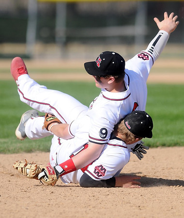 Pat Christman<br /> Mankato West's Connor Wollenzien falls over teammate Josh Cook after catching an infield fly ball during the first game against Faribault Friday.