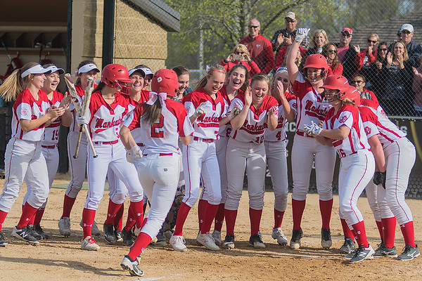 The Mankato West softball team gathers around home plate in celebration after Holly Wiste (2) hit a grand slam home run against Mankato East during Friday's rivalry matchup. Photo by Jackson Forderer