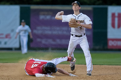 Alex Turner (2) of Mankato East throws the ball to first base as Kyle Looft (15) of Mankato West tries his best to disrupt Turner with a takeout slide. West defeated East 12-0 in Tuesday's game. Photo by Jackson Forderer