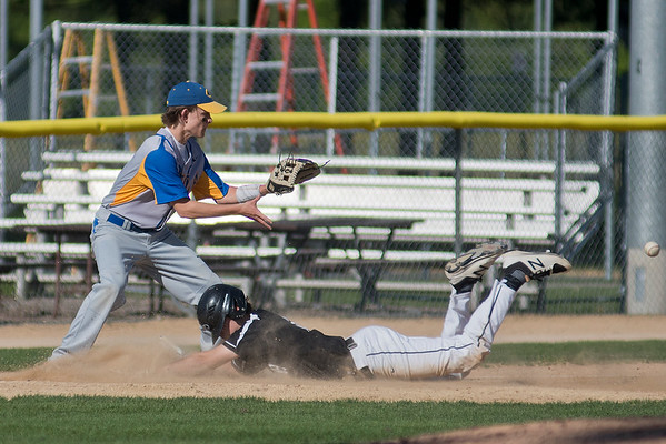 Carter Fogal of Mankato Loyola waits for the throw to third base as Martin County West's Colton Leiding slides headfirst into the base. Photo by Jackson Forderer