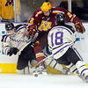 The University of Minnesota's Brady Skjei kicks at the puck as Minnesota State University's Chase Grant (21) and Matt Leitner (18) defend him during the first period Saturday at the Verizon Wireless Center.