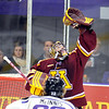 University of Minnesota goalie Adam Wilcox reaches up to grab the puck during the first period against Minnesota State University Saturday.