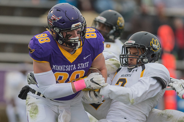 Wayne State's Demetrius Stinson tries to strip the ball away from Minnesota State's Trevor Nissen (88) as Nissen went in for a go-ahead touchdown during Saturday's game. The Mavericks rallied from a 27-27 tie to win 48-27. Photo by Jackson Forderer