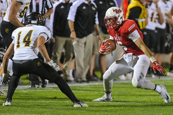 Mankato West's Wesley Henderson tries to get past Mankato East's Aidan Koprowski (14) at the annual East-West football game played at Blakeslee Stadium. Mankato West will face Waconia for a chance to go to the state tournament. Photo by Jackson Forderer