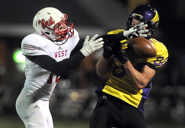 Pat Christman<br /> Mankato West's Connor Watts gets a hand in front of Chaska receiver Calvin Buesgens during their Section 2AAAAA championship game Friday in Chaska.