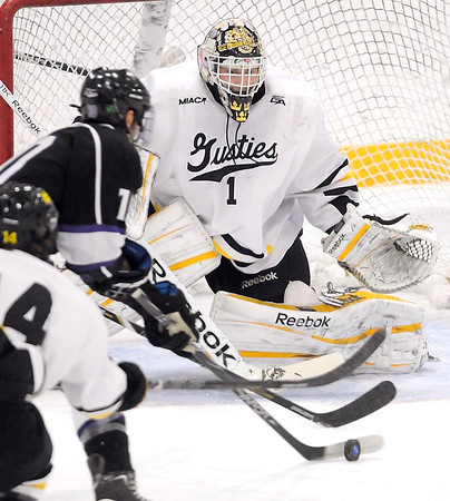 Gustavus Adolphus College goalie John McLean keeps an eye on University of St. Thomas' Travis Baker during the first period Friday at Don Roberts Ice Rink. McLean was injured and had to leave the game near the end of the first period.