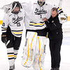 Gustavus Adolphus College goalie John McLean gets help leaving the ice from a trainer and teammate Adam Smyth near the end of the first period against the University of St. Thomas Friday at Don Roberts Ice Rink.