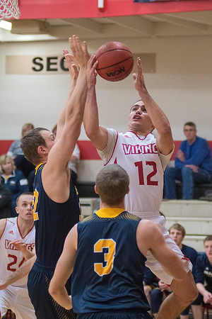 Brady Rose (12) of Bethany Lutheran goes up for a shot against Buena Vista's Adam Juhl (3) and Matthew Goodman during the Vikings home opener on Wednesday. Photo by Jackson Forderer