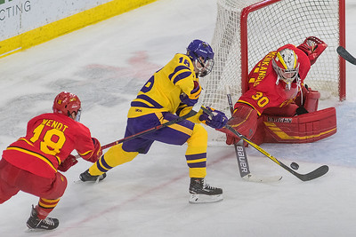 Minnesota State's Reggie Lutz tries to handle a bouncing puck in front of Ferris State goalie Roni Salmenkangas while being prodded by defensemen Hunter Wendt in the second period. The Mavericks offense imposed their will on the Bulldogs and won the WCHA conference game 7-1. Photo by Jackson Forderer