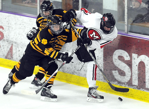 Mankato West's Derek Frentz is pursued by Mankato East/Loyola's Austin Claude behind the net during the first period Thursday at All Seasons Arena.