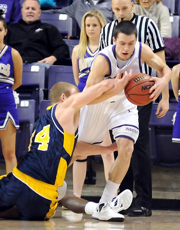 Mounty Mercy's Scott Odekirk (14) and Minnesota State's Zach Monaghan (22) scramble for a loose ball during the first half Saturday at Bresnan Arena.