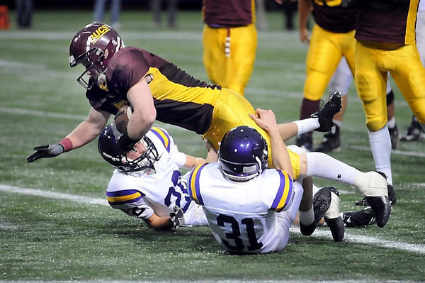 Blue Earth Area's Bailey Olson gets over two Rochester Lourdes defenders for a four quarter touchdown.