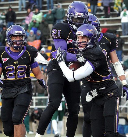Minnesota State's Justin Otto is helped up by teammateEarl Brooks after making an interception in the end zone during the second overtime of their NCAA Division II Super Regional tournament game against Northwest Missouri State Saturday at Blakeslee Stadium.