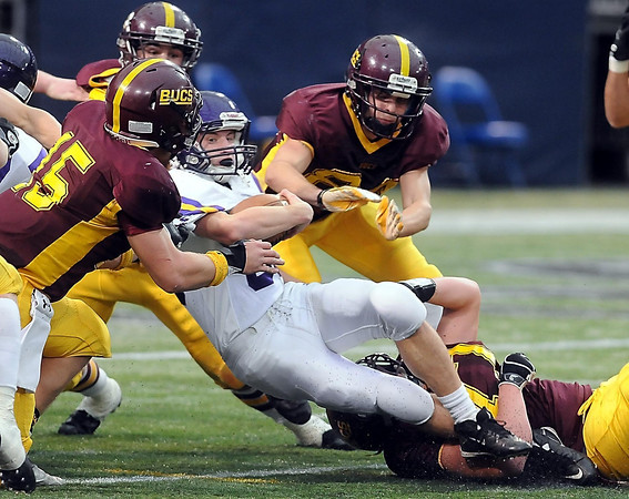 Rochester Lourdes player Kane Carstens is tackled by a swam of BEA Buccaneers.