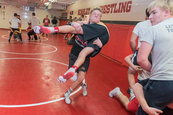 Rhett Wiebers (center) picks up his sparring partner during practice at the Mankato West wrestling room on Wednesday. Wiebers is a senior who will be wrestling in the 152-pound weight division. Photo by Jackson Forderer