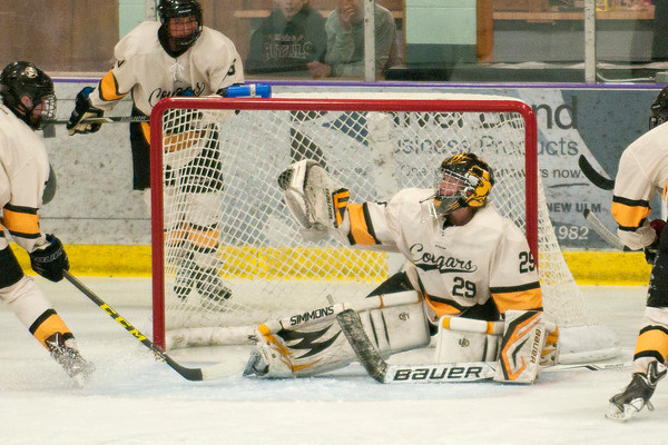 Goalie Jack Cusey makes a glove save during Mankato East's game against Hutchinson. East won in overtime by a score of 3-2. Photo by Jackson Forderer