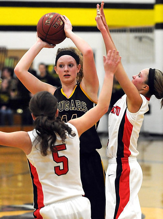 Mankato West's Megan Svir (5) and Lexi Schoper (1) surround Mankato East's Claire Ziegler during the first half Tuesday at the East gym.