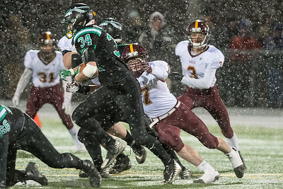 Blue Earth Area's Zach Buseman (7) chases down Pipestone's Garrett Ploeger (34) during the first half of Friday's state quarterfinal game played in New Ulm. The windy, snowy weather played a factor in the game, slowing down both offenses. Photo by Jackson Forderer