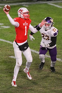 Mankato West's Jack Foster (1) throws the ball to a receiver while being chased by Waconia's Cade Mueller (23). West will face Apple Valley in the quarterfinals of the Class AAAAA football tournament. Photo by Jackson Forderer