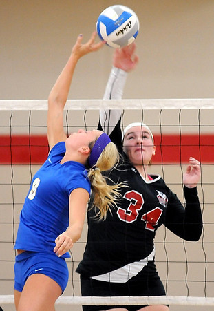 Bethany Lutheran College's Shelby Wiederhoeft (34) and St. Scholastica's Erica Birkeland reach for the ball above the net during their match Saturday.