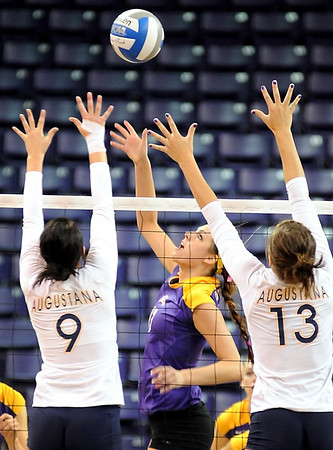 Minnesota State's Jill Storlie tips the ball over the block of Augustana's Courtney Ysker (9) and Taylor Hrdlichka (13) during their match Saturday at Bresnan Arena.