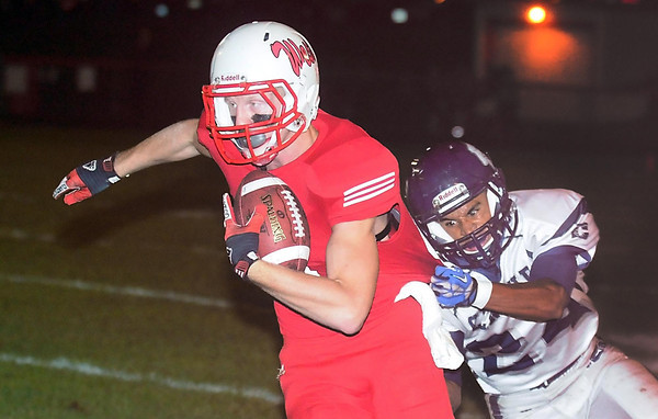 Pat Christman <br /> Mankato West's Will Claussen slips out of the grasp of Rochester Century's Darryl Martin for a touchdown during the first half Friday at Todnem Field.