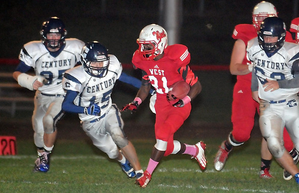 Pat Christman <br /> Mankato West's Cory Johnson slips through the Rochester Century defense during a touchdown run in the first half Friday.