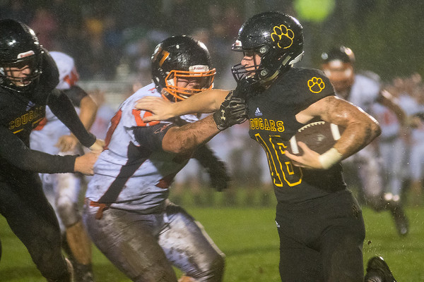 Mankato East's Jack Clifford (16) carries the ball and gives a stiff arm to Winona's Koltan Benrud during Friday's game. Photo by Jackson Forderer