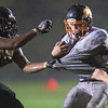 Lutherking Marc (63) of Mankato East grabs the jersey of Winona's Dan Jonsgaard during Friday's game. The Cougars lost 32-8 to the undefeated Winhawks of Winona. Photo by Jackson Forderer