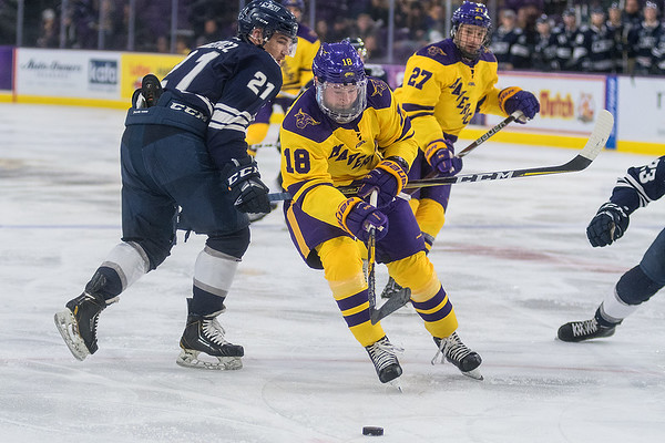 Minnesota State's Ian Scheid (18) drives towards the net while being defended by Mount Royal's Kord Pankewicz in the second period of play during Saturday's exhibition game. The Mavericks won the game 7-3. Photo by Jackson Forderer