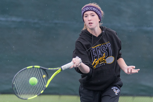 Katelyn Flatgard of Mankato East hits a forehand in the number three singles match during the Cougars' match against New Ulm. The match was moved indoors to St. Peter due to inclement weather. Photo by Jackson Forderer