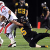 Mankato East's Brent Adams tries to bring down Mankato West quarterback Ryan Schlichte during the first half Wednesday at Blakeslee Stadium.