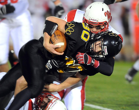 Mankato East's Cody Lorentz pushes for extra yards as Mankato West's Isaac Weber tries to bring him down during the first half Wednesday at Blakeslee Stadium.