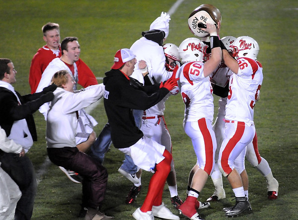 Mankato West's Conor Wanderscheid (50) and Tyler Jakes (56) hoist the Kato Jug as fans storm the field after West's win over crosstown rival Mankato East 44-0 Wednesday at Blakeslee Stadium.