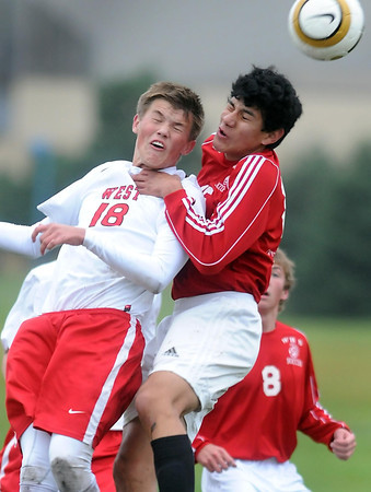 Pat Christman <br /> Mankato West's DIllon Lambert and Worthington's Jesus Montego leap for the ball during the first half of their Section 2A semifinal game Tuesday at the Dakota Meadows field.