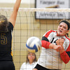 Pat Christman <br /> Mankato West's Megan Hulscher (14) hits the ball past Mankato East's Sami Erickson (5) during their second game Tuesday at the West gym.