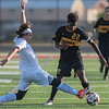 Suleiman Haji (22) of Mankato East squeaks past Worthington's Chris Cerda during the first half of the Section 2A boys soccer championship game. East lost to Worthington 2-1. Photo by Jackson Forderer