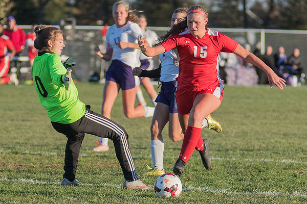 Mankato West's Katie Roberts (15) dribbles the ball past New Ulm goalie Kendra Nesvold to give herself a wide open net, on the way to West's first goal of the game. The Scarlets won 4-1 to advance to the Section 2A finals. Photo by Jackson Forderer