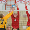 Mankato East's Mackenzie Schweim (left) tries to tip the ball over Mankato West's Kayla Grunst (15) and Ellie Blackman (1) during Tuesday's match played at West. The Scarlets won the contest in three straight games. Photo by Jackson Forderer