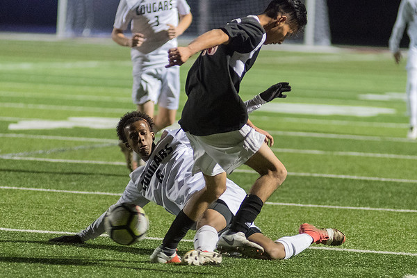 Mankato East's Isak Abader makes a tackle slide on Worthington's Jose Aguirre in the first half of Thursday's Section 2A final match. The Cougars lead 1-0 at the end of the first half, but gave up two goals in the second half to lose 2-1. Photo by Jackson Forderer