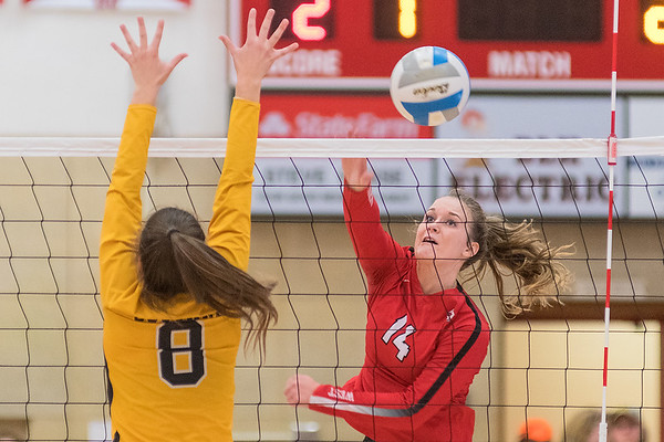 Mankato West's Kenzie Grunst hits a spike down the line past Mankato East's Rachel Clifford during Tuesday's match played at West. Photo by Jackson Forderer