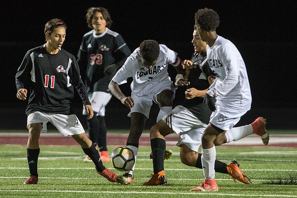 Mankato East's Suleiman Haji (center) fights for the ball against Worthington's Guadalupe Padilla (11) and Anthony Euceda (second from right) in the second half of Thursday's Section 2A finals. Photo by Jackson Forderer