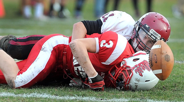 New Prague's Ben Buthe watches the ball bounce free after tackling Mankato West's Derek Frentz during the first half Saturday.