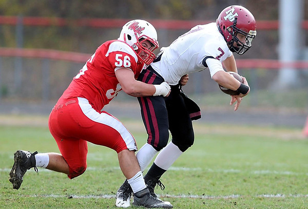 Mankato West's Tyler Jakes brings down New Prague quarterback Kyle Stepka during the first half of Saturday's Section 2AAAAA semifinal game at Todnem Field.