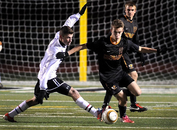 Mankato East's Albert Podshivaylov kicks the ball past Rochester Lourdes' Jack Convery during their State Class A quarterfinal match Friday at Roseville High School.
