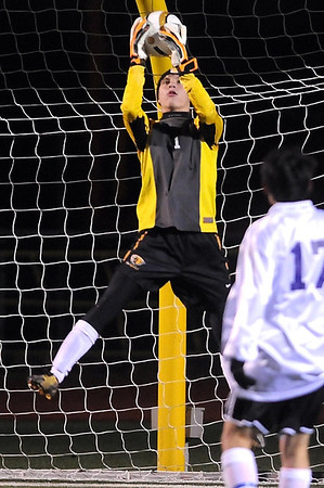 Mankato East goalie Nick Olson makes a save as Rochester Lourdes' Kalvin Kim watches during the first half of their State Class A quarterfinal match Friday at Roseville High School.