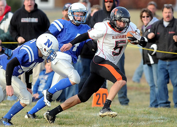 Madelia quarterback Adam Cooling slips through the Nicollet defense during the first half Saturday in Nicollet.