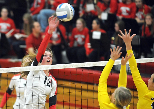 Pat Christman<br /> Mankato West's Molly Lohman hits the ball past a pair of Hutchinson defenders during their second game Wednesday at the West gym.