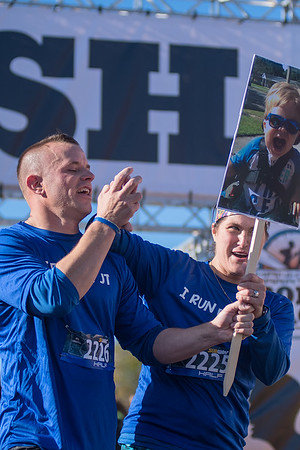 Gave Cornish (left) and Sarah Cornish hold hands and hold up a sign with their nephew JT Young after crossing the finish line in the Mankato half marathon. Young has spinal muscular atrophy. Photo by Jackson Forderer