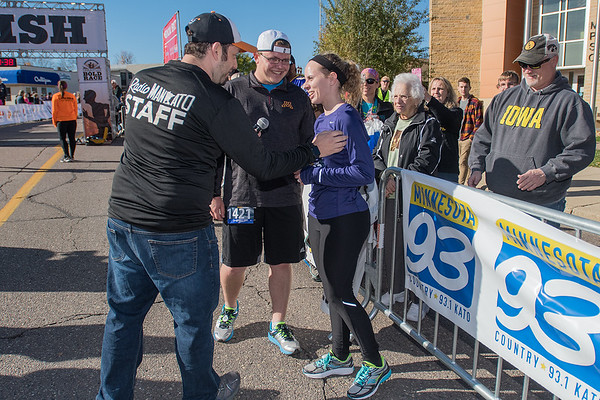 Alex Zellmer (center) and Hannah Whitington get interviewed by Radio Mankato after Zellmer proposed to Whitington at the finish line. It was Zellmer's second half marathon and Whitington's first. Whitington said yes. Photo by Jackson Forderer